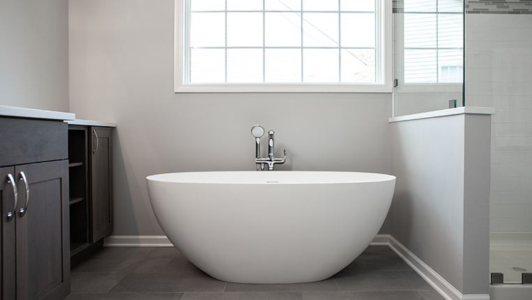 Freestanding white modern bathtub with chrome finishes.