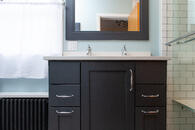 small bathroom remodel with black cabinets and chrome hardware with a double-sink and painted floor heater