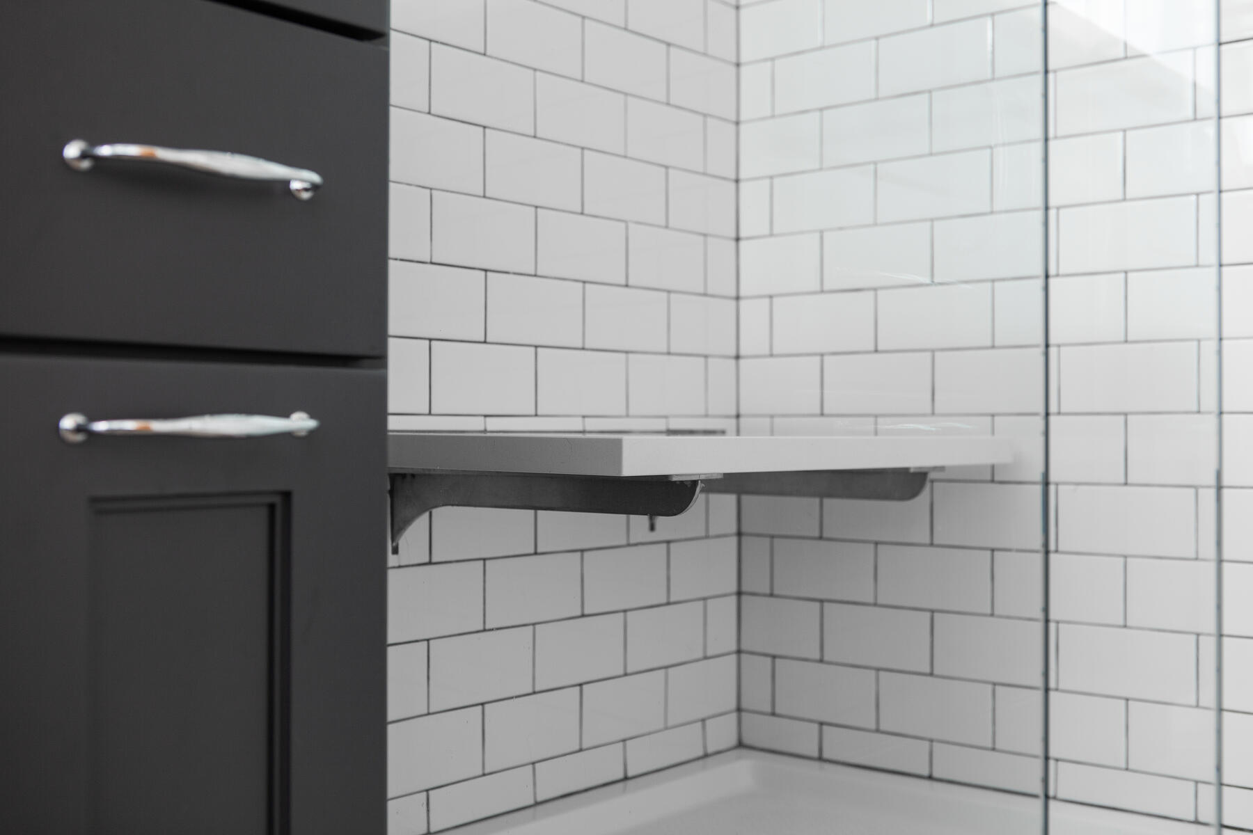 Classic white subway tile make a small bathroom feel larger and compliments the black cabinetry