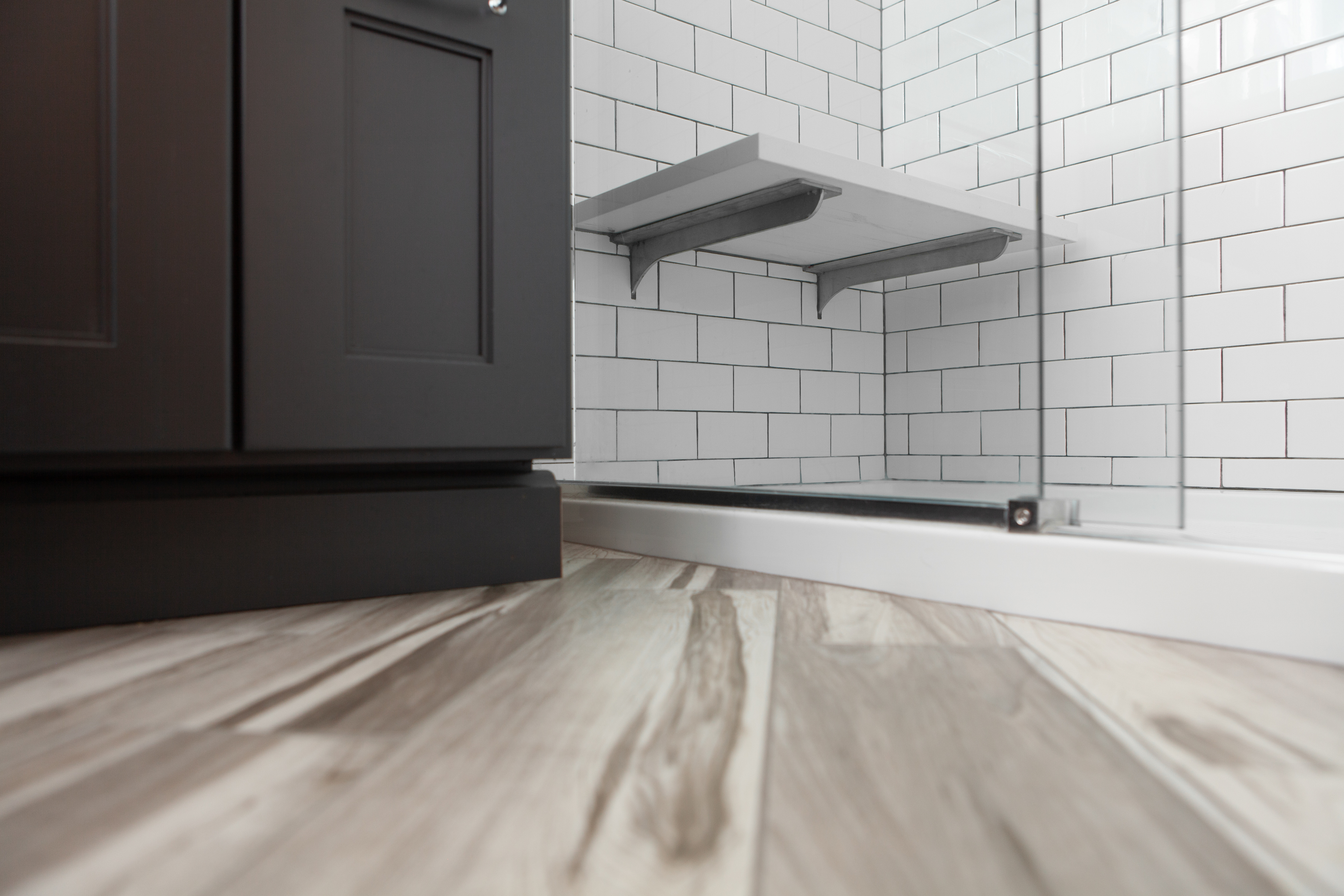 Painted black cabinetry contrasting beautiful hardwood floors and the simplicity of white subway shower tiles