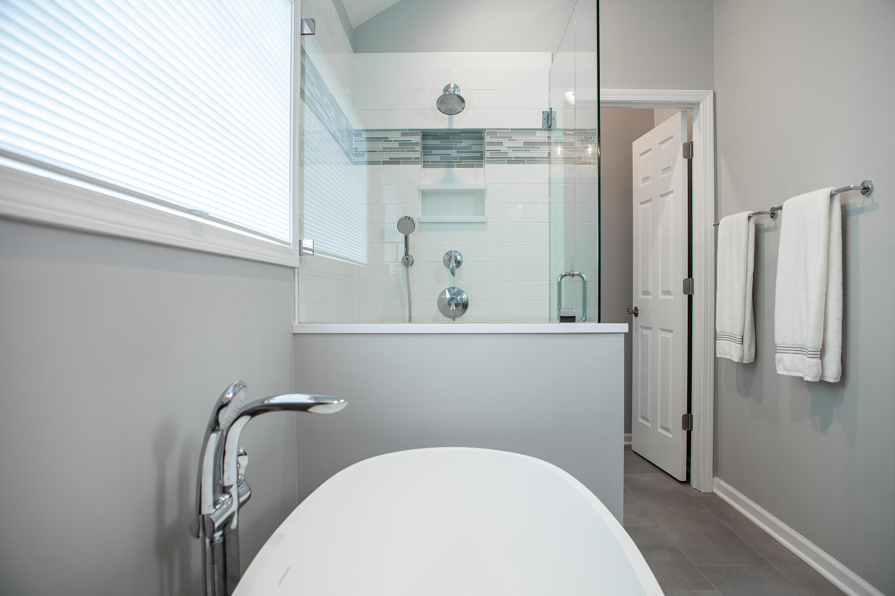Beautiful modern bathroom remodel in Lake Zurich with white tub and glass shower surround..