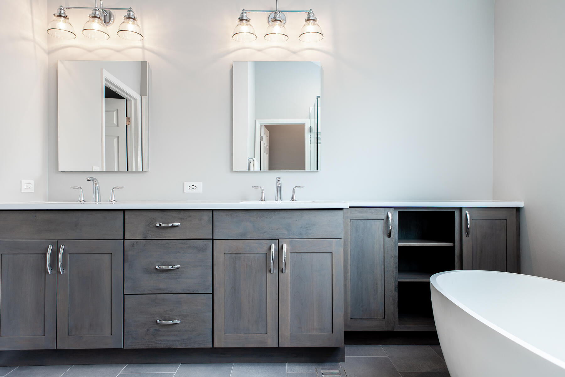Beautiful modern bathroom remodel in Lake Zurich with natural gray cabinets, chrome finishes and white tub.