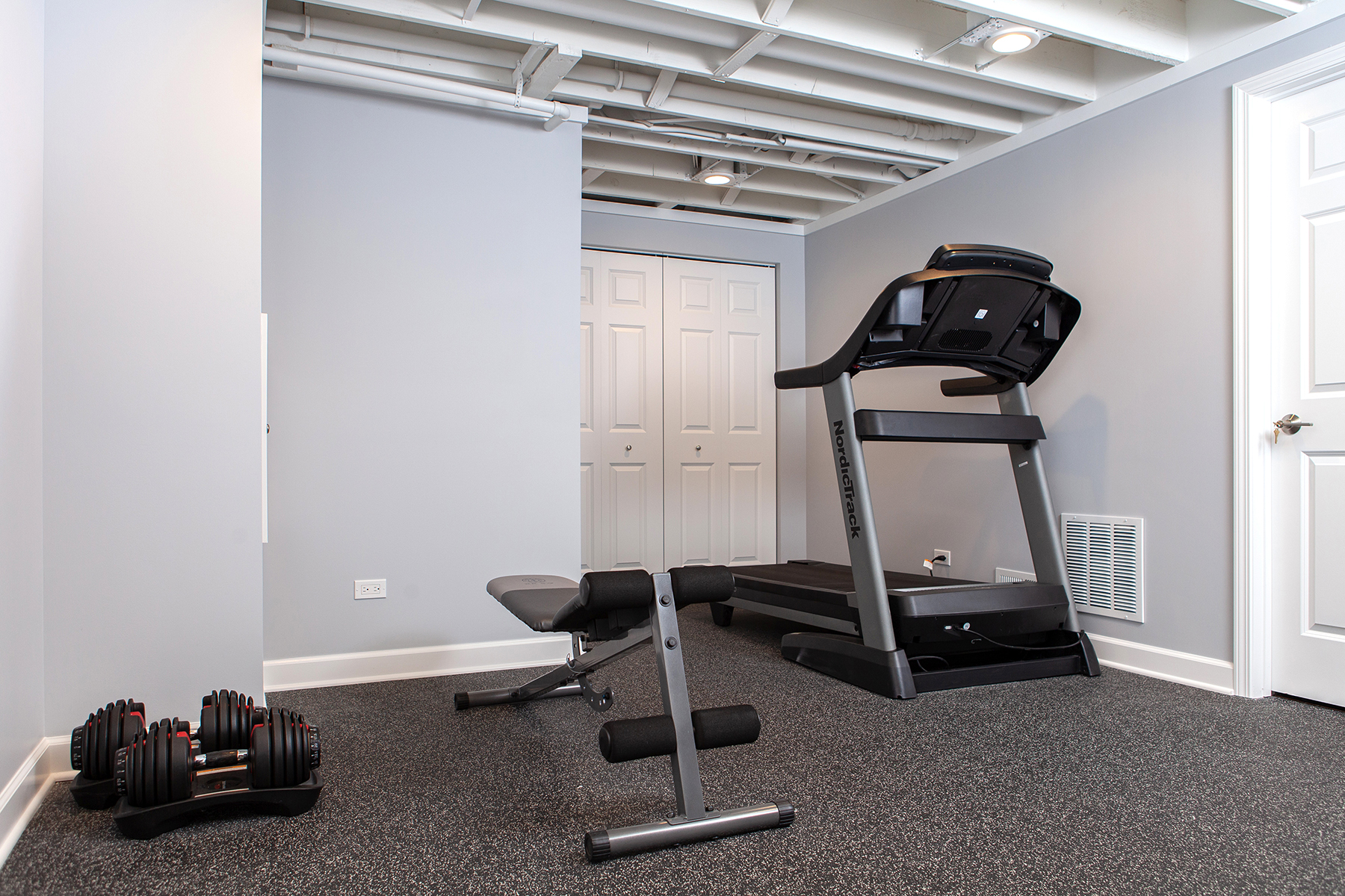 Remodeled basement workout room in Libertyville, Illinois with treadmill, free-weights and padded floors.