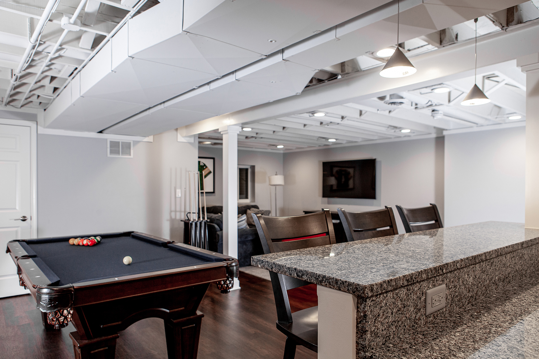 Remodeled basement in Libertyville, Illinois with hardwood floors, pool table, workout room, lounge area and kitchen.