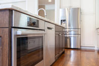Beautiful kitchen remodel with a large wooden island with lower microwave and dishwasher.