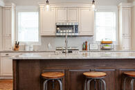 Beautiful kitchen remodel with white cabinets natural stone countertops and a large wooden island with seating.