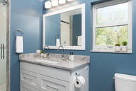Classic style in this hall bath remodel in Libertyville, Illinois with blue walls, white cabinetry, chrome hardware and gray countertops.