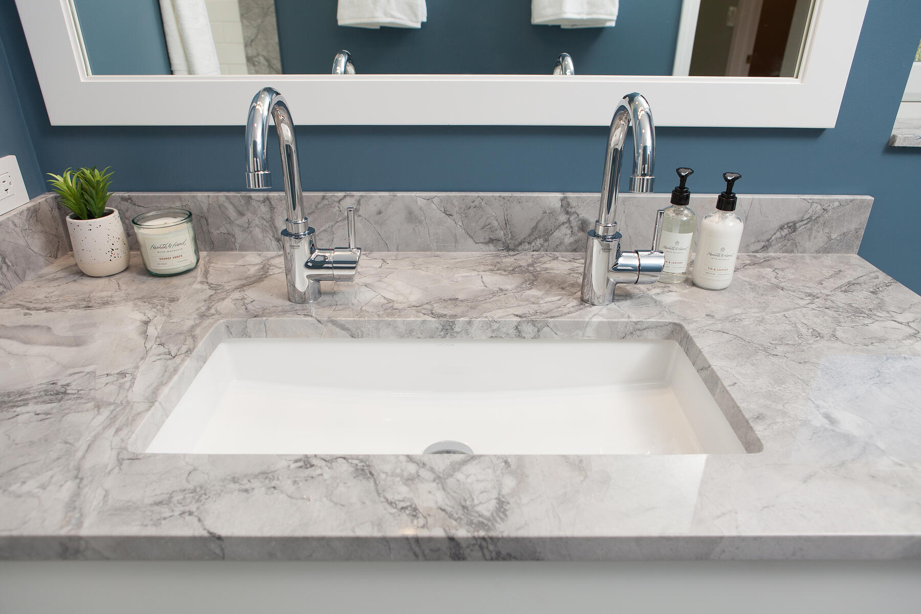 Classic style in this hall bath remodel in Libertyville, Illinois with blue walls, white mirror, chrome hardware and gray countertops including double faucets with a single basin sink.