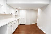 Remodeled basement with custom white cabinetry, hardwood flooring, light gray wall paint and lots of windows throughout.