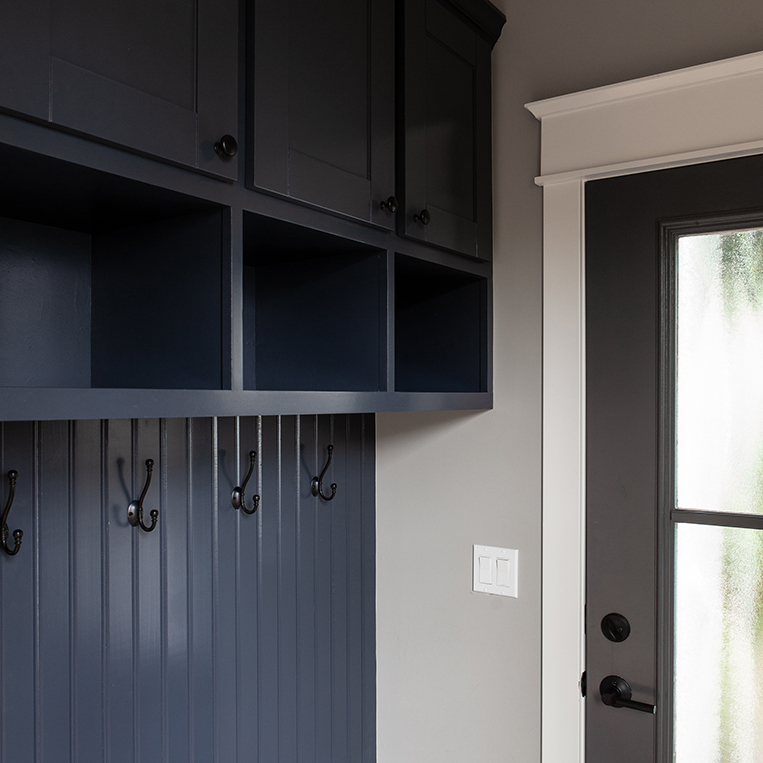 Navy blue cabinetry with coat hooks and gray walls in this beautiful mudroom by BDS Design Build Remodel.