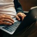 Man sitting typing on a laptop.