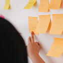 BDS team member pointing at a board of sticky notes with the work process outlined.
