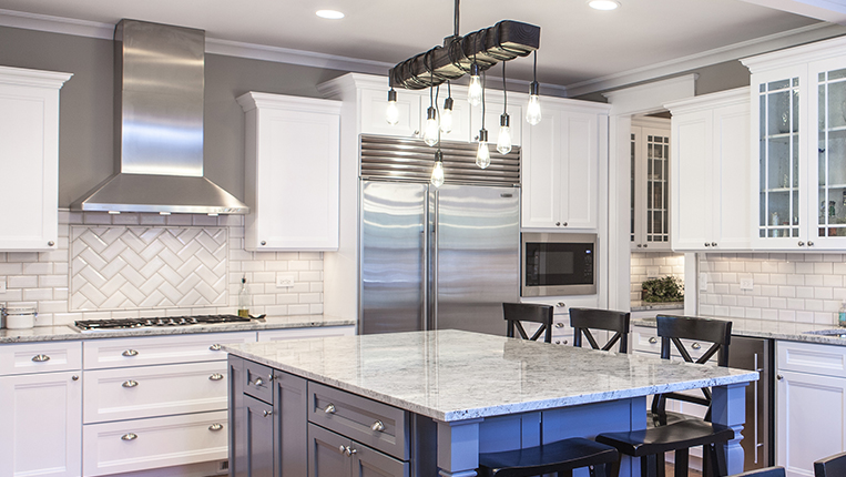 Gray granite kitchen countertops with white cabinets and a slate grey island.