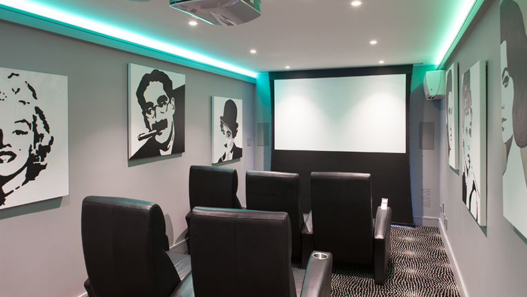 Basement home theater with gray walls, black theater seating, large projection screen and classic black and white movie posters on the walls.