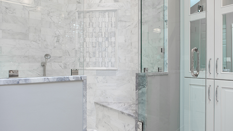 Large shower with glass door and marble gray and white tiles.