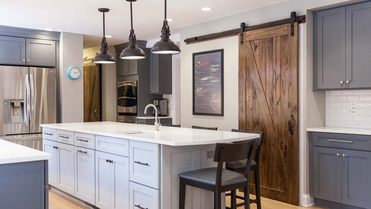 Kitchen island with black lights and white counter-tops