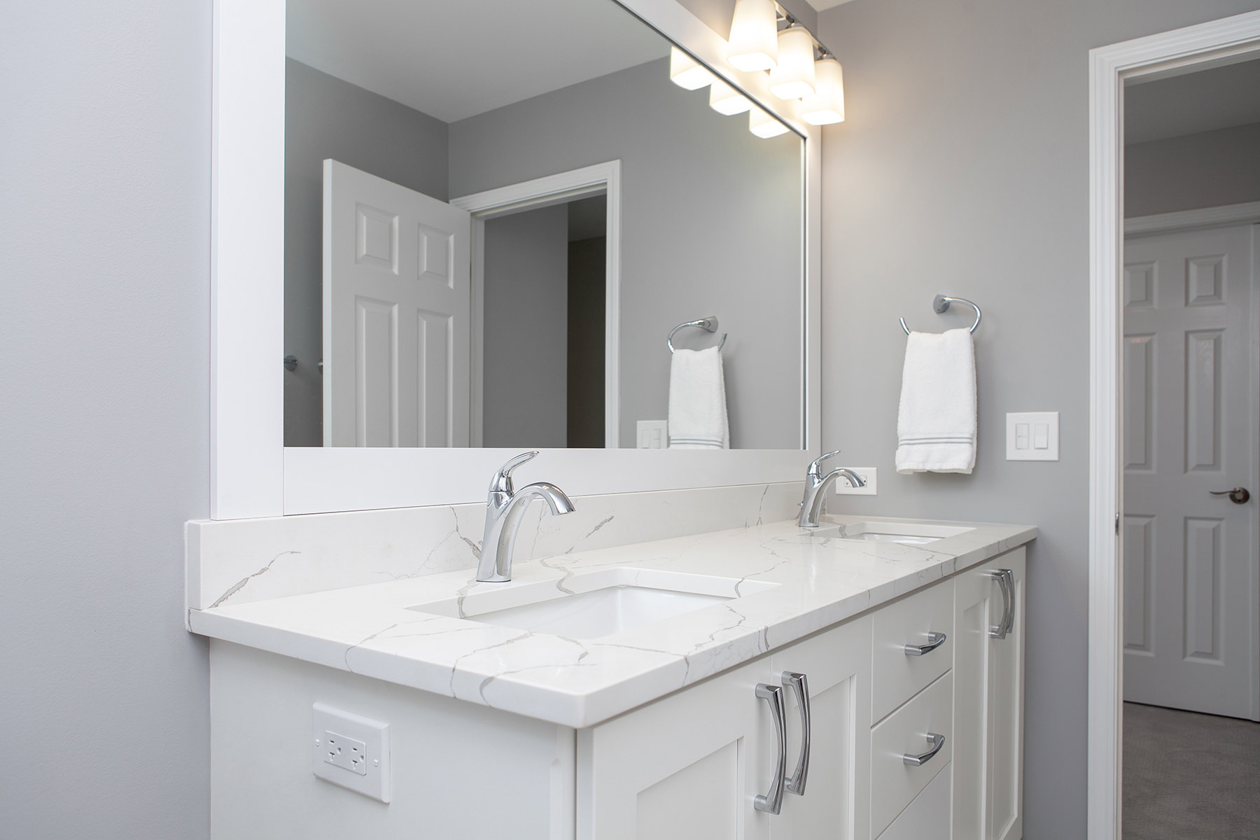 remodeled home bathroom with white cabinetry, light gray countertops and chrome finishes
