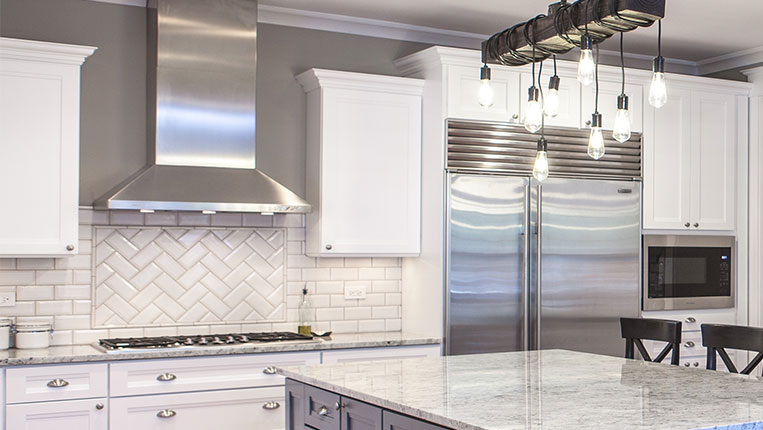 Updated kitchen with herringbone white tiled backsplash