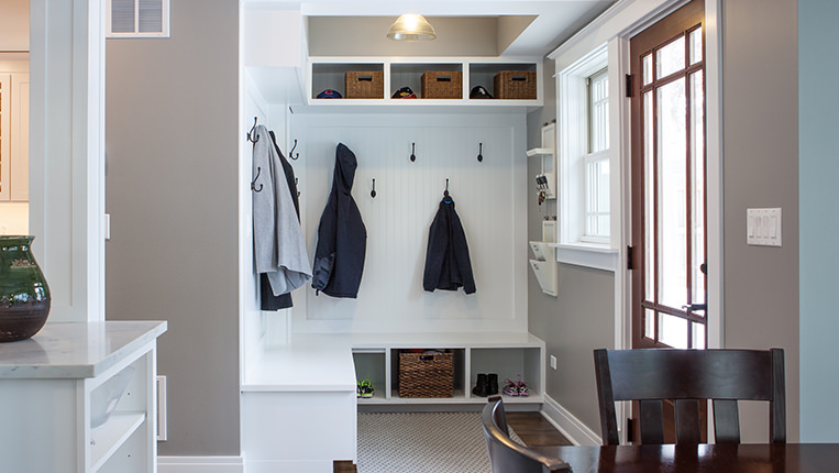 Beautiful home mudroom off the front entryway with white bead-board, coat hangers, and storage nooks.