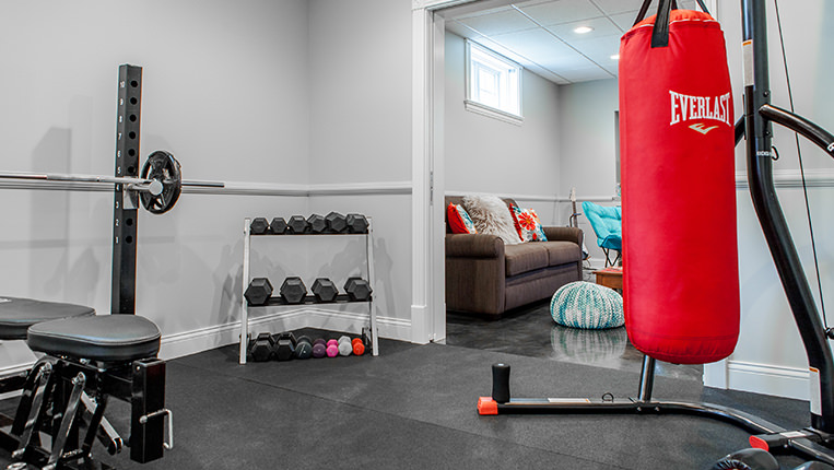 Remodeled room into a home gym with black rubber floors, free-weight rack, and a red boxing bag.